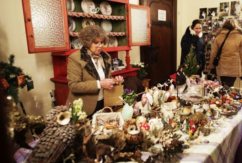 Señora con un puesto de productos artesanos en el mercado de la casa Koïfhus [Fuente: http://www.noel-colmar.com]